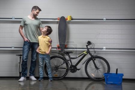 Photo pour Père et fils souriants debout ensemble dans l'atelier avec vélo et planche à roulettes - image libre de droit