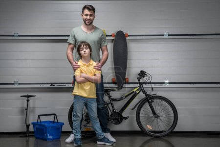 Photo for Smiling father and confident son standing in workshop with bicycle and skateboard - Royalty Free Image