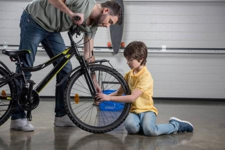 Photo for Side view of father and little son checking tire of bicycle - Royalty Free Image