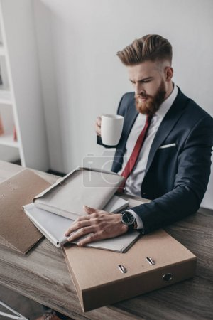 Photo for Young businessman with documents and folders drinking coffee and sitting at table in office - Royalty Free Image