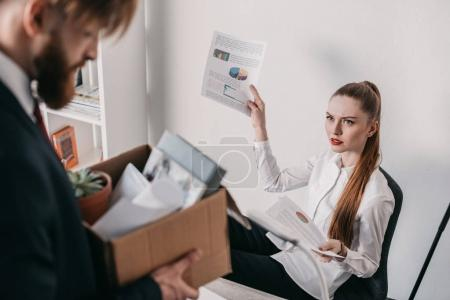 Photo for Young upset fired businessman with cardboard box and angry businesswoman in office - Royalty Free Image