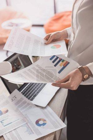 Photo pour Vue latérale d'une jeune femme d'affaires, lecture des documents commerciaux et graphiques au bureau - image libre de droit