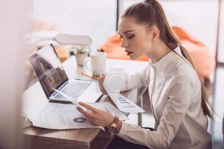Photo pour Jeune femme d'affaires concentré lecture des documents et assis à table dans le Bureau - image libre de droit