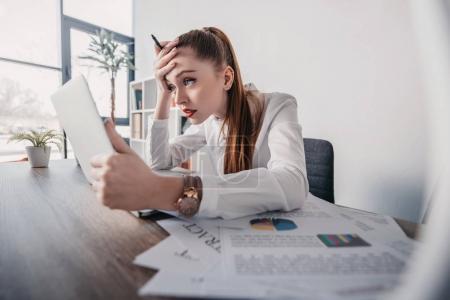 Photo pour Jeune femme d'affaires stressée avec ordinateur portable et documents assis à la table dans le bureau - image libre de droit