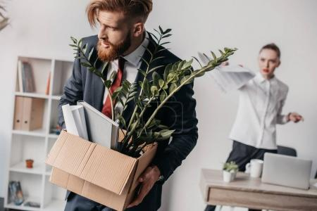 Photo for Young upset fired businessman with cardboard box in office, angry boss behind - Royalty Free Image