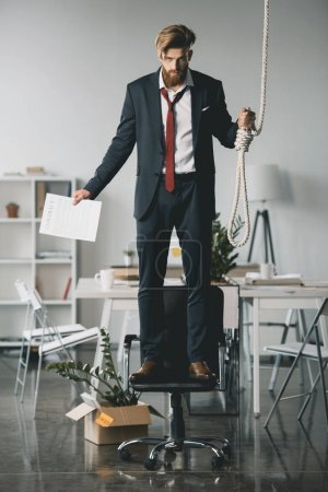 Photo for Young fired businessman standing on chair and trying to hang himself in office - Royalty Free Image