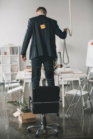 Photo pour Vue arrière d'un homme d'affaires viré debout sur une chaise et essayant de se pendre au bureau - image libre de droit