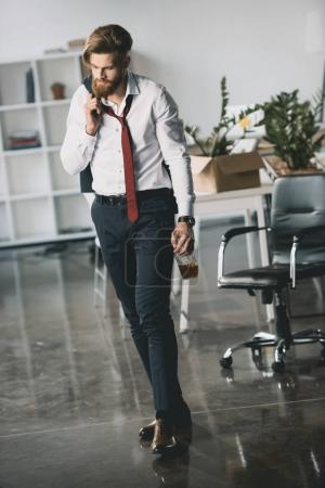 Photo for Drunk young businessman holding bottle of whiskey in office - Royalty Free Image