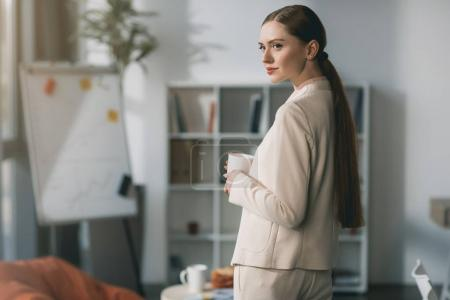 Photo for Side view of attractive young businesswoman holding cup and looking away in office - Royalty Free Image