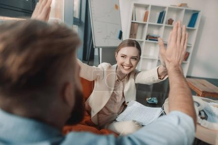 Photo for Happy young businessman and businesswoman giving double high five in office - Royalty Free Image