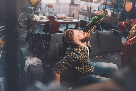 Photo pour Barbu de jeune homme avec la gueule de bois boire de la bière de bouteille dans la chambre malpropre après la fête - image libre de droit