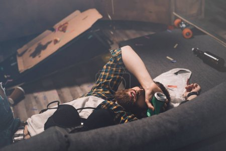 Photo for Drunk bearded young man sleeping on couch with bra and beer can after party - Royalty Free Image