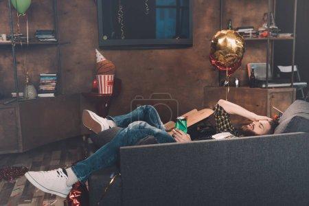 Photo pour Bu barbu jeune homme avec des yeux fermés, couché sur le canapé après la fête - image libre de droit