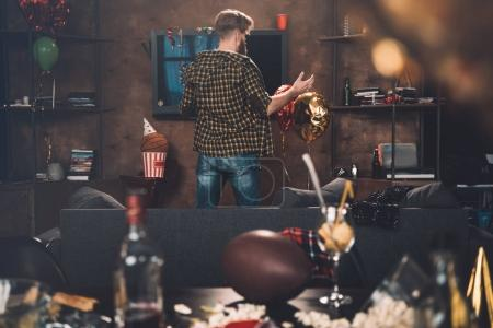 Photo for Back view of confused young man gesturing while standing in messy room after party - Royalty Free Image
