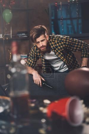 Foto de Hombre joven barbudo estresado con resaca sosteniendo la botella en la habitación desordenada después de la fiesta - Imagen libre de derechos