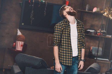 Foto de Joven barbudo de pie con los ojos cerrados y gritando después de la fiesta - Imagen libre de derechos