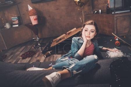 Photo for Young upset woman with hangover sitting on couch in messy room after party - Royalty Free Image
