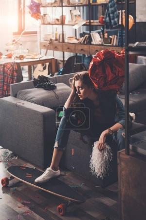 Foto de Joven mujer molesta con resaca sentada en el sofá en la habitación desordenada después de la fiesta - Imagen libre de derechos