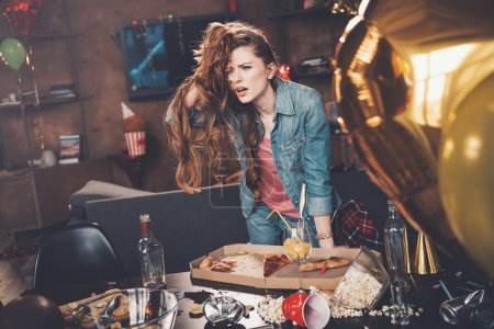 Photo for Depressed young woman with hangover leaning at messy table after party - Royalty Free Image