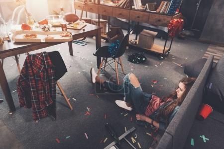 Foto de Vista de ángulo alto de la joven borracha acostada en el suelo en la habitación desordenada después de la fiesta - Imagen libre de derechos