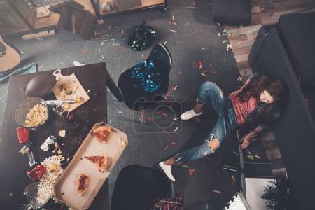 Foto de Vista superior de la joven borracha tumbada en el suelo en la habitación desordenada - Imagen libre de derechos