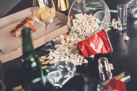 Photo for Close-up view of popcorn, glasses and trash on messy table after party - Royalty Free Image