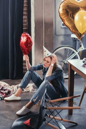 Foto de Mujer joven confundida sosteniendo globo en la habitación desordenada después de la fiesta - Imagen libre de derechos