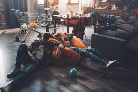 Photo for Tired man and woman resting on beanbag chair in messy room after party - Royalty Free Image