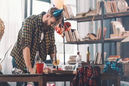 Foto de Hombre con resaca limpieza habitación desordenada después de la fiesta - Imagen libre de derechos