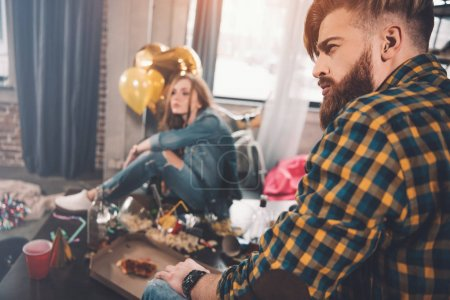 Photo for Couple with hangover sitting in messy room after party - Royalty Free Image