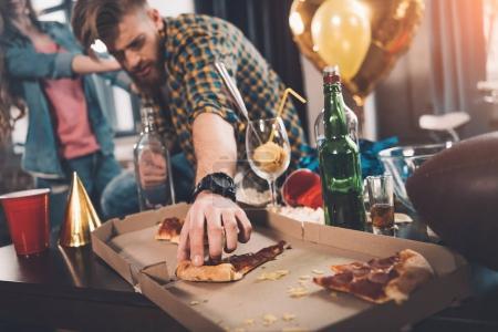 Foto de Hombre comiendo pizza rancio en habitación desordenada después de la fiesta - Imagen libre de derechos