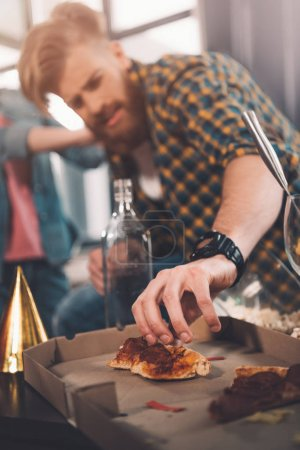 Photo for Man eating stale pizza in messy room after party - Royalty Free Image