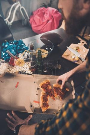 Photo for Top view of man eating stale pizza in messy room after party - Royalty Free Image