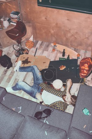 Photo for Drunk bearded man lying on floor in messy room after party - Royalty Free Image