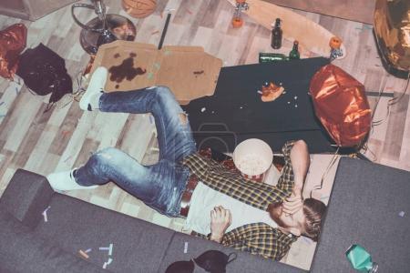 Foto de Hombre barbudo borracho acostado en el suelo en la habitación desordenada después de la fiesta - Imagen libre de derechos