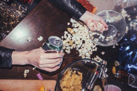 Foto de Mujer comiendo palomitas de maíz en la habitación desordenada después de la fiesta - Imagen libre de derechos