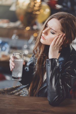 Woman with hangover with medicines