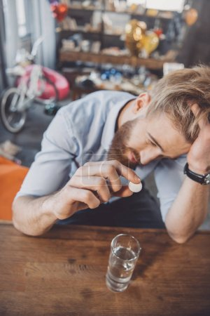 man with hangover with medicines