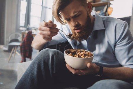 Photo pour Flocons de maïs homme fatigué manger à la maison après la fête - image libre de droit