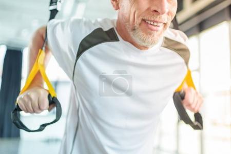 Photo pour Entraînement sportif senior avec bande de résistance dans le centre sportif - image libre de droit