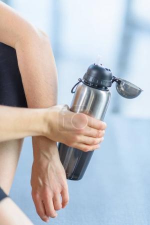 sportswoman holding sport bottle