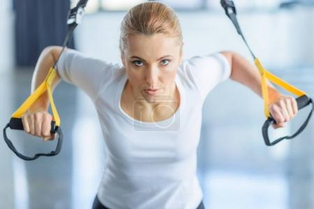 Photo for Concentrated sportswoman training with resistance band in sports center - Royalty Free Image