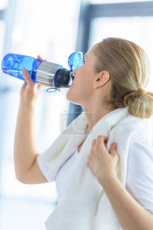 Photo for Sportswoman with towel drinking water from sport bottle in sports center - Royalty Free Image