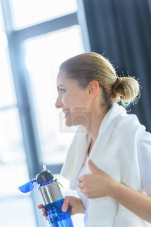 Photo for Sportswoman with towel holding sport bottle in sports center - Royalty Free Image