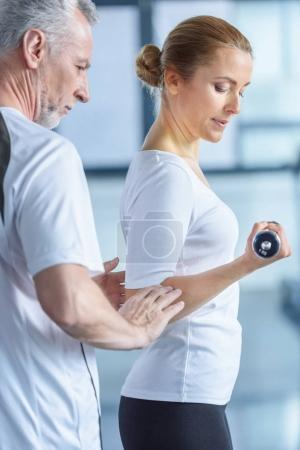 sportswoman and senior trainer with dumbbells