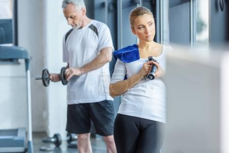 Photo for Sportswoman and senior sportsman training with dumbbells in sports center - Royalty Free Image