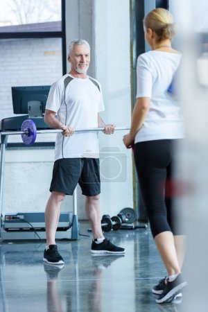 Man with barbell and sportswoman in gym