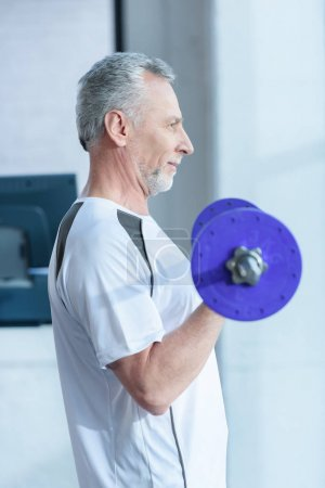 Photo for Side view of bearded mature sportsman training with barbell in gym - Royalty Free Image