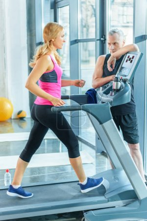 Trainer and sportswoman in gym