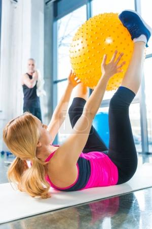 Photo for Mature sportsman looking at sporty woman exercising with fitness ball in gym - Royalty Free Image